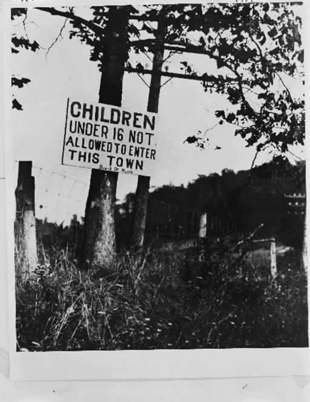 Photo of a sign prohibiting children under 16 from entering a town during the polio outbreak.