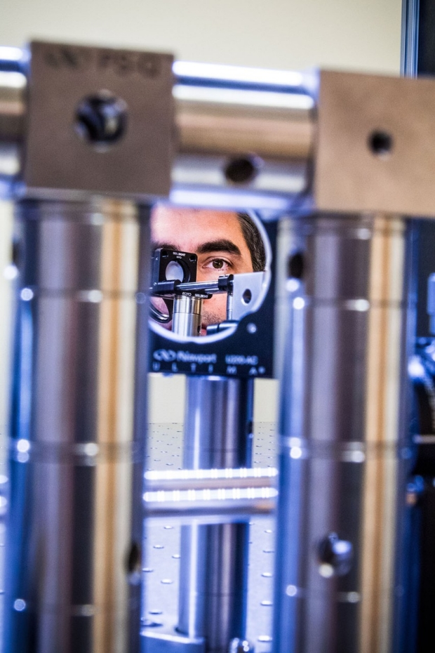 Man's face looking into the mirror of an adaptive optics microscope