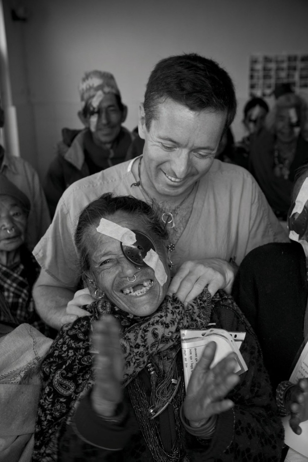Man standing behind a laughing patient whose left eye is covered with a patch