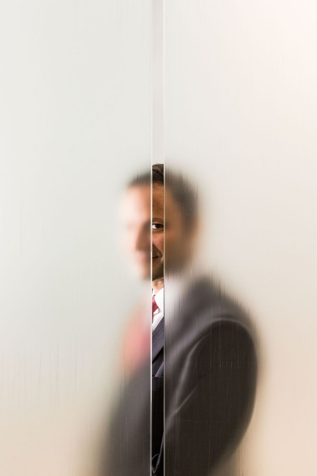 Man standing behind opaque glass looking through a vertical slit
