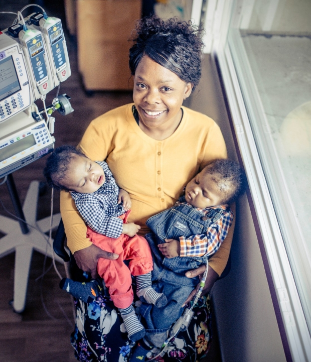 Rosemary Anama, holding her sleeping grandsons Levi and Ronnie Dogan