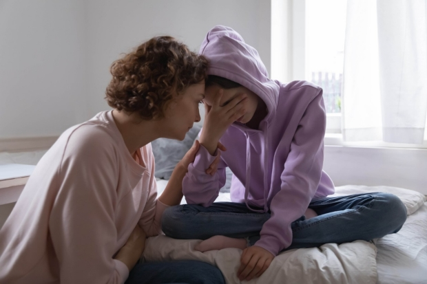 Image of a woman comforting an anxious child. By fizkes