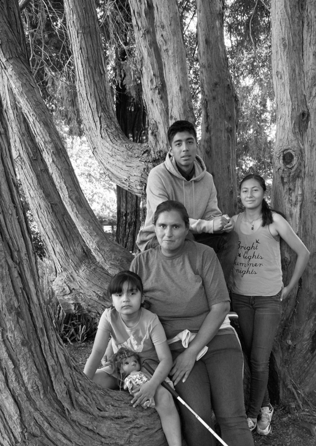 Mother with her two daughters and a son, standing by a tree