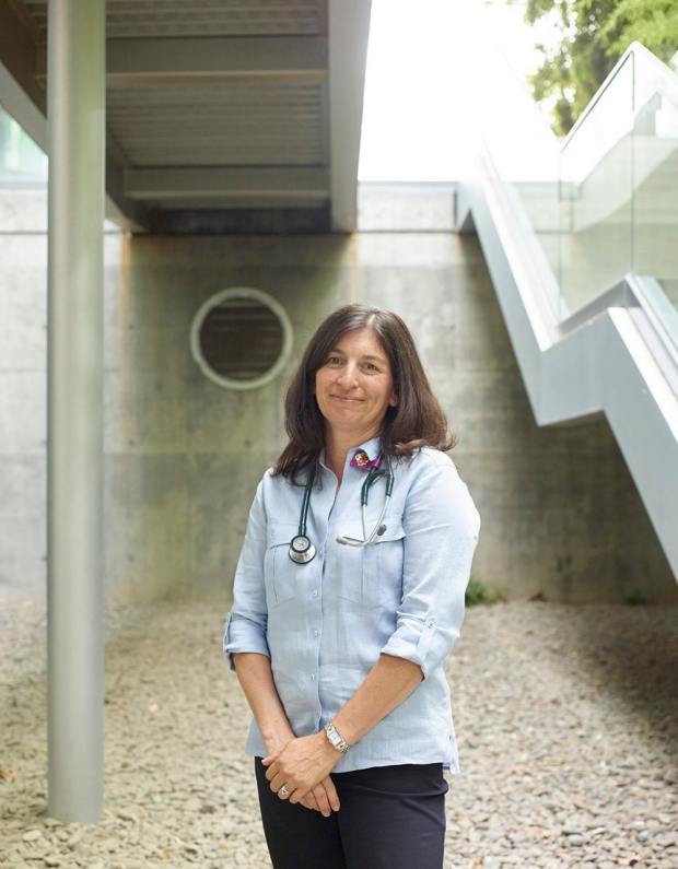 Woman with a stethoscope around her neck standing in front of a building