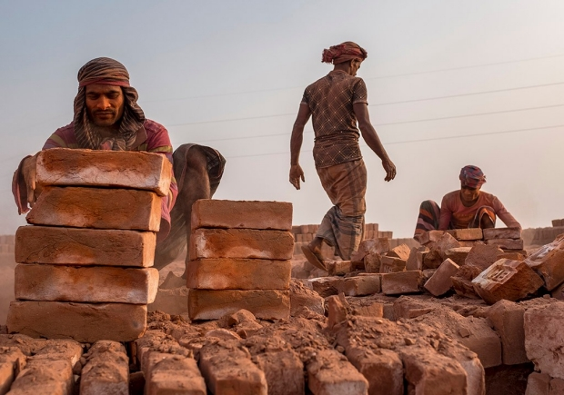 Workers stack fired bricks